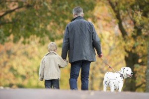 picture of father and son walking the dog