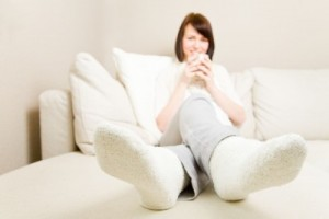 Young woman drinking hot coffee and resting her feet