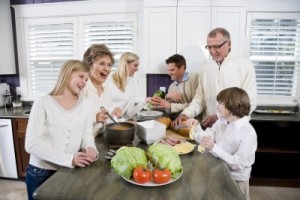 picture of Three generation family in kitchen serving lunch, talking and laughing