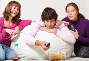 picture of Three cheerful teens watching TV and laughing