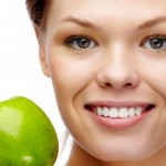 picture of smiling woman white teeth holding green apple