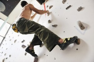 picture of young and fit man exercise free mountain climbing on indoor practice wall