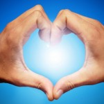 picture of hands in heart loving sign towards sun