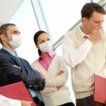 picture of Group of associates in protective masks looking strictly at coughing man