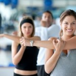 picture of Woman doing stretching exercises for her arm at the gym