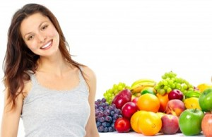 picture of Young smiling woman with fruits and vegetables. Over white background