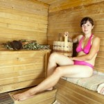 picture of Young woman sitting on wooden bench at sauna