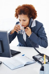 picture of Female executive having glass of water while talking on phone
