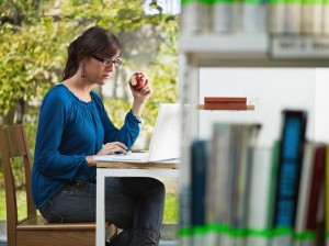picture of female college student studying in library and eating red apple. Horizontal shape, side view, three quarter length