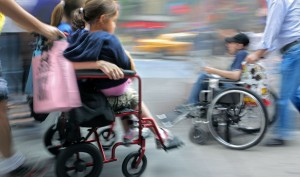 picture of two handicapped persons, woman holding daughter on laps and senior moving on a wheelchairs with family assistants in motion blur