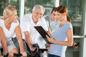 picture of Fitness trainer talking to senior citizens on bikes in gym