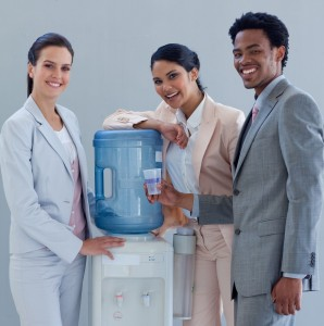 picture of Smiling business people with a water cooler in office