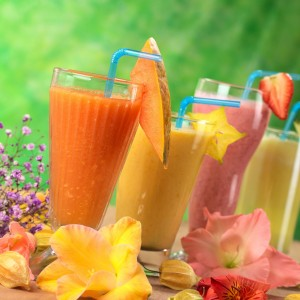 picture of Fresh papaya, mango, strawberry and pineapple fruit juices and milkshakes decorated with flowers (Selective Focus, Focus on the papaya juice and the papaya slice garnish)