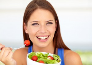 Lovely young woman enjoying a healthy green salad