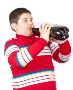 A fat young man drinking soda from a plastic bottle isolated over white background