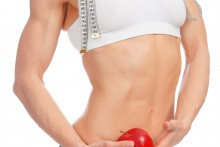 Muscular woman with apple and tape measure posing against white background