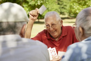 picture of Active retirement, old people and seniors free time, group of three elderly men having fun and playing cards game at park