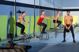 CrossFit gym members jump on boxes while one swings a kettle bell. CrossFit training is a combination of moves and exercises designed to improve the overall ability of the body - strength, balance, speed, etc.